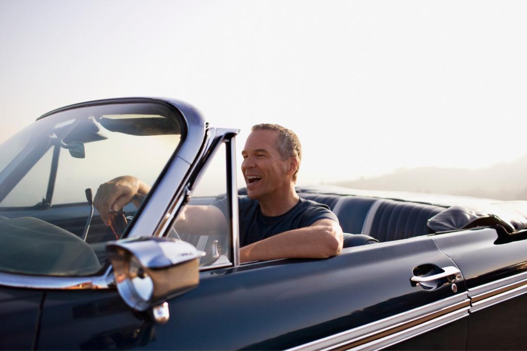 older man drives convertible car while listening to Bon Jovi
